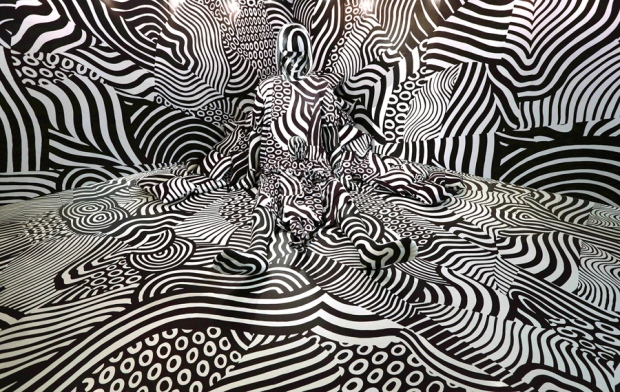"Model feebee poses as part of art installation ""Narcissism : Dazzle room"" made by artist Shigeki Matsuyama at rooms33 fashion and design exhibition in Tokyo, Wednesday, Sept. 14, 2016. Matsuyama's installation features a strong contrast of black and white, which he learned from dazzle camouflage used mainly in World War I. (AP Photo/Eugene Hoshiko)"